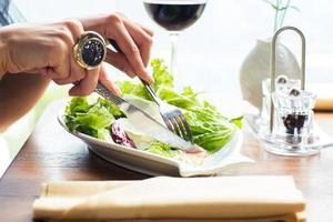 weibliche Hände, die Salat essen foto