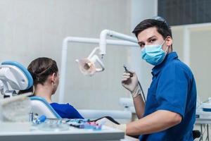 Zahnarzt, der eine Patientin heilt foto