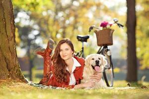 hübsche junge Frau, die mit Hund in einem Park liegt