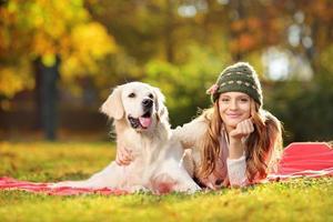 hübsche Frau, die mit ihrem Hund in einem Park liegt foto