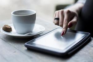 weibliche Hand, die auf Tablette durchsucht foto