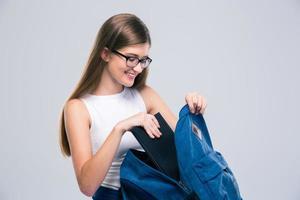 weiblicher Teenager, der etwas im Rucksack sucht foto