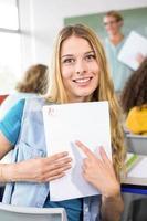 schöne Studentin, die auf Papier zeigt