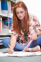 Studentin, die in der Bibliothek studiert foto