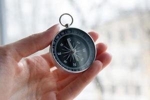 schwarzer Kompass in einer weiblichen Hand foto