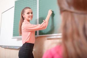 junge Lehrerin, die an die Tafel schreibt foto