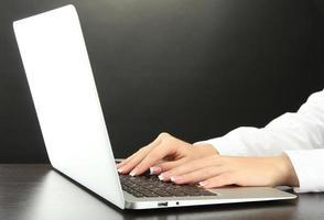 weibliche Hände schreiben auf Laptot, Nahaufnahme foto