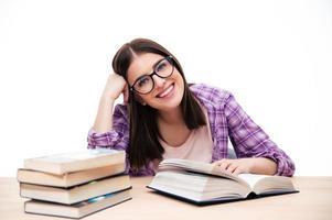 glückliche Studentin, die am Tisch sitzt