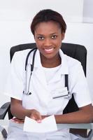Ärztin, die Rezeptpapier am Schreibtisch gibt foto