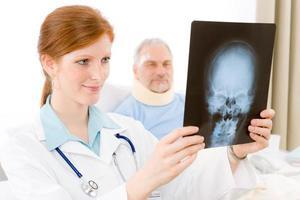 Krankenhaus - Ärztin untersucht Patientenröntgen foto