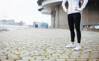 Fitness-Frau, die auf Bürgersteig in der Stadt steht