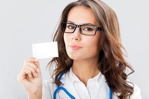 junge Ärztin, die leere Visitenkarte zeigt foto