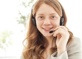 Porträt der glücklichen jungen Frau mit Headset