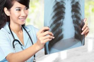 Ärztin, die eine Röntgenaufnahme untersucht foto