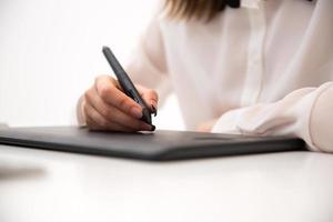 weibliche Hände, die auf Grafiktablett arbeiten
