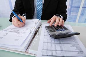 Geschäftsmann, der Rechnung am Schreibtisch berechnet foto