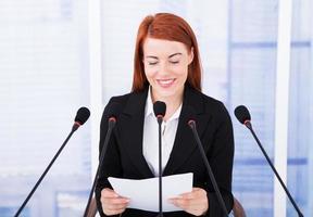 lächelnde Geschäftsfrau, die Rede auf Konferenz hält foto