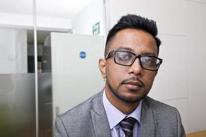 Nahaufnahmeporträt des indischen Geschäftsmannes, der Brille mit Bart trägt foto