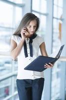 Geschäftsfrau auf Handy liest aus Ordner foto