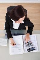glückliche Geschäftsfrau, die Steuer berechnet foto