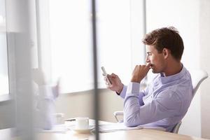 lässig gekleideter Geschäftsmann mit Handy im Büro foto