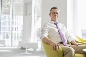 Porträt des selbstbewussten Geschäftsmannes, der an der Bürolobby sitzt foto