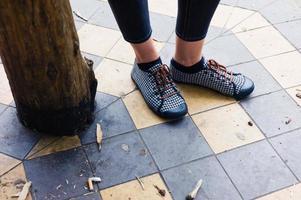 Füße der jungen Frau, die durch hölzernen Pfosten steht foto