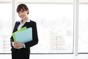 junge lächelnde Geschäftsfrau, die im Büro arbeitet foto