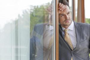 nachdenklicher Geschäftsmann, der weg schaut, während er sich auf Glastür stützt foto