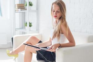 Porträt der Geschäftsfrau mit Ordner, der im Büro auf sitzt foto
