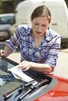 frustrierter weiblicher Autofahrer, der Parkticket betrachtet foto