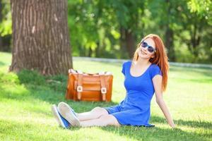 rothaariges Mädchen mit Koffer im Park. foto