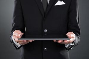 Geschäftsmann, der digitales Tablett hält foto