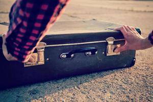 Frau öffnet einen Koffer foto