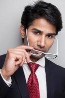selbstbewusster Geschäftsmann, der Brille abnimmt