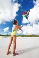 kleines Mädchen fliegt einen Drachen foto