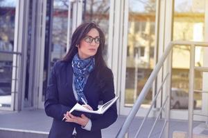 Geschäftsfrau, die außerhalb des Bürogebäudes steht foto