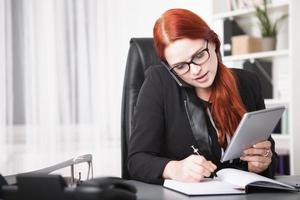 junge Geschäftsfrau, die im persönlichen Organisator anruft und schreibt foto