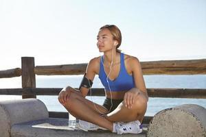 Fitnessfrau, die an der Küste ruht