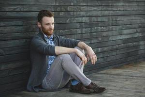 schöner junger Mann, der auf dem Holzboden sitzt foto