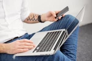 beschäftigter Mann, der mit Computer und Handy arbeitet foto