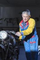 Mann schiebt ein Motorrad foto