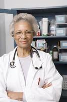 selbstbewusster leitender Arzt, der mit verschränkten Armen in der Klinik steht