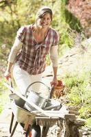 Frau mit Schubkarre, die draußen im Garten arbeitet foto