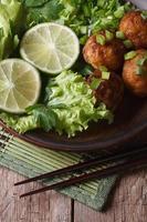 Fischbällchen mit Limette und Salat und Essstäbchen in Nahaufnahme. Vertikale