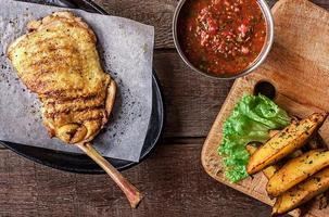 gebratenes Hühnerfleisch am Knochen, Kartoffelschnitze, Salat foto