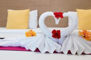 weiße Schwäne aus Handtüchern auf dem Bett im Hotel