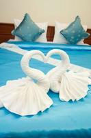 Handtuchdekoration in Form von weißen Schwänen im Hotelzimmer im thailändischen Stil foto