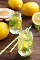frische Limonade mit Zitrone auf braunem Holzhintergrund foto