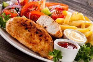 Gegrillte Hähnchenfilets, Pommes Frites und Gemüse auf weißem Hintergrund
